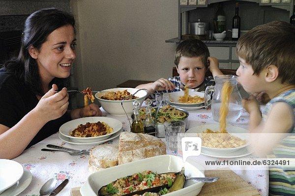 Mutter mit zwei Kindern sitzen am Tisch & essen Tagliatelle
