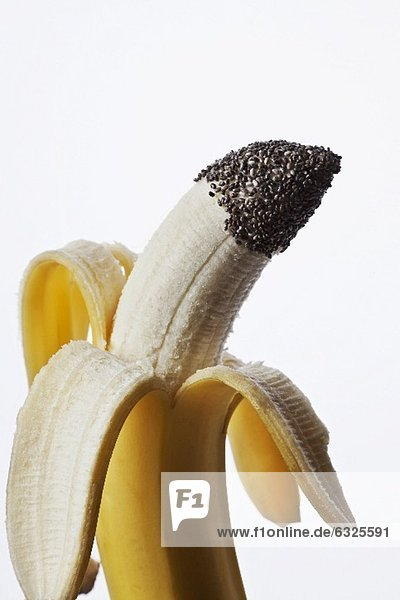 Halb geschälte Banane mit Chia-Samen