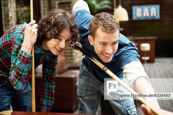 Zwei Freunde spielen Pool in der Bar