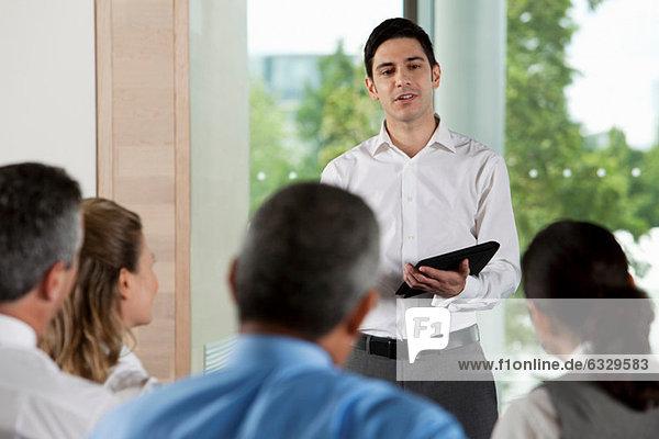 Mann mit digitalem Tablett im Geschäftstreffen