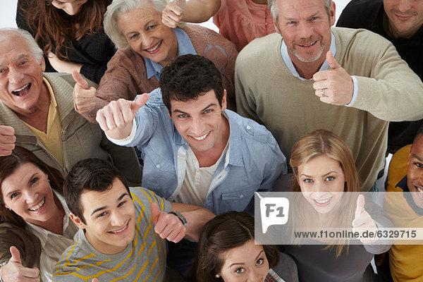 Gruppe von Personen  die mit erhobenem Daumen auf die Kamera schauen  hoher Winkel