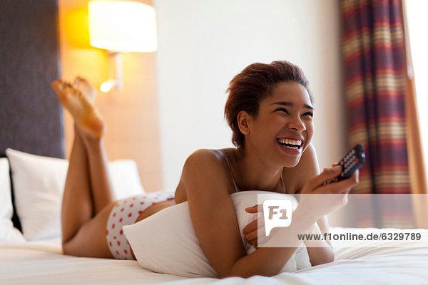 Junge Frau auf dem Bett liegend mit TV-Fernbedienung