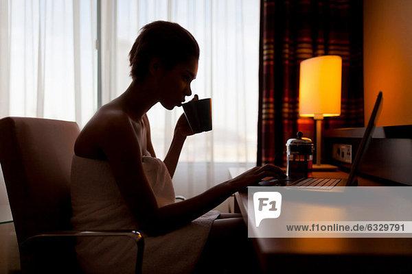 Junge Frau sitzt am Laptop im Hotelzimmer