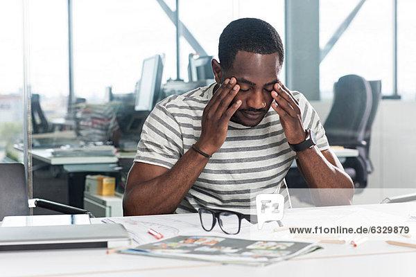 Besorgt aussehender Mann mit Plänen auf dem Schreibtisch
