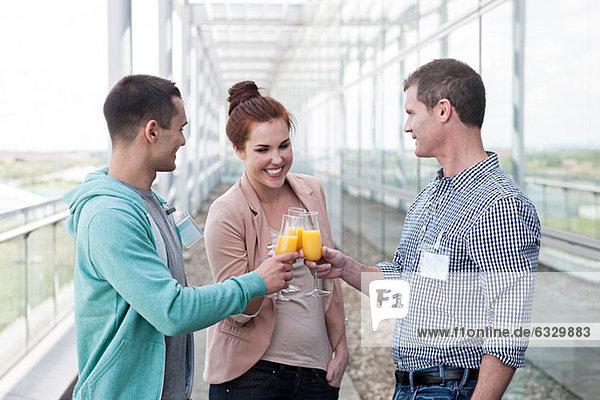Kollegen toasten mit Orangensaft