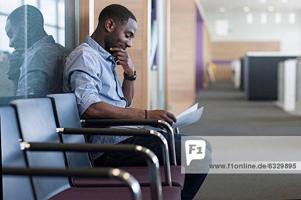 Mann sitzt auf Stuhl und liest Dokument