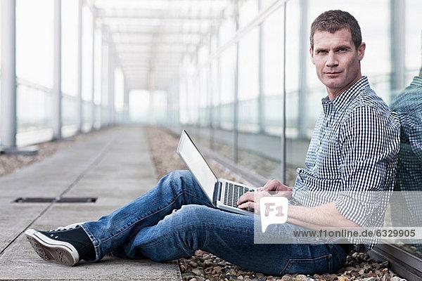 Mann auf dem Boden sitzend mit Laptop