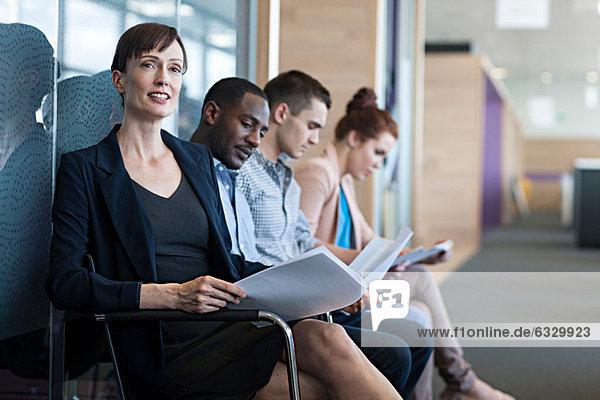 Vier Personen sitzen auf Stühlen mit Dokumenten