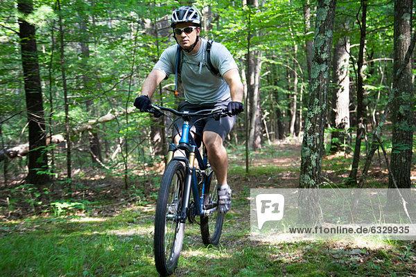 Mann Mountainbiken im Wald