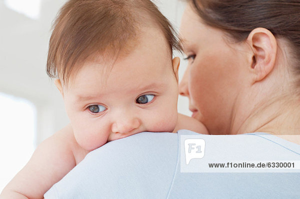 Kleines Mädchen auf Mutters Schulter
