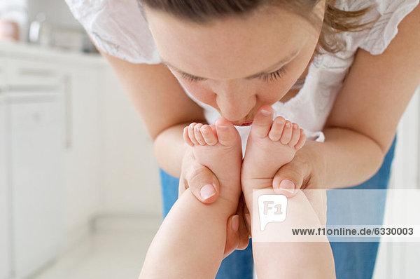Mutter küsst die Füße des Babys