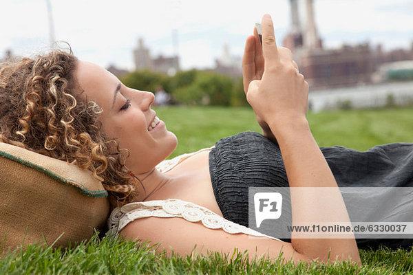 Junge Frau liegt auf Gras und schaut auf das Smartphone