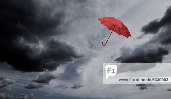 Roter Regenschirm schwebt durch bewölkten Himmel