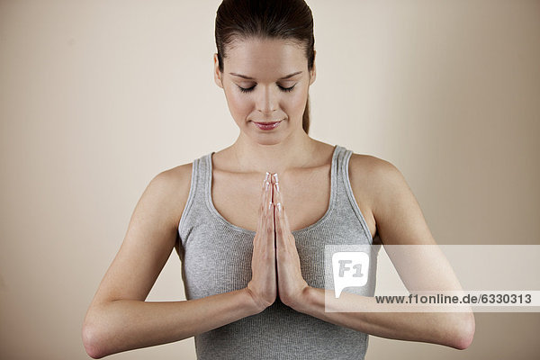 A young woman meditating  hands in prayer position