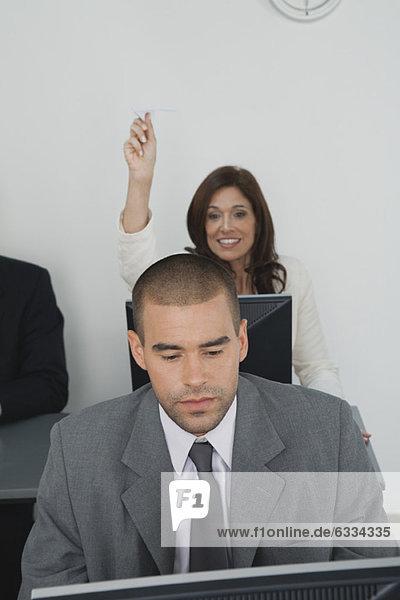 Geschäftsfrau wirft Papierflugzeug nach männlichem Kollegen