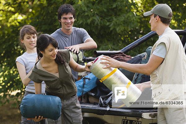 Junge Camper entladen ihre Campingausrüstung von der Rückseite des Pickups