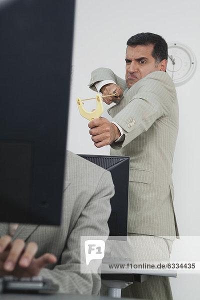 Geschäftsmann mit Schleuder auf Kollegen gerichtet