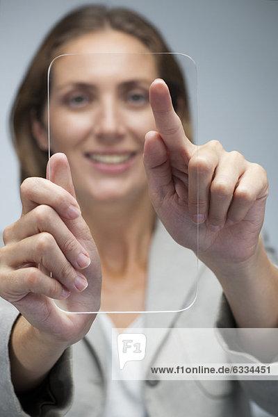 Geschäftsfrau mit transparentem digitalem Tablett