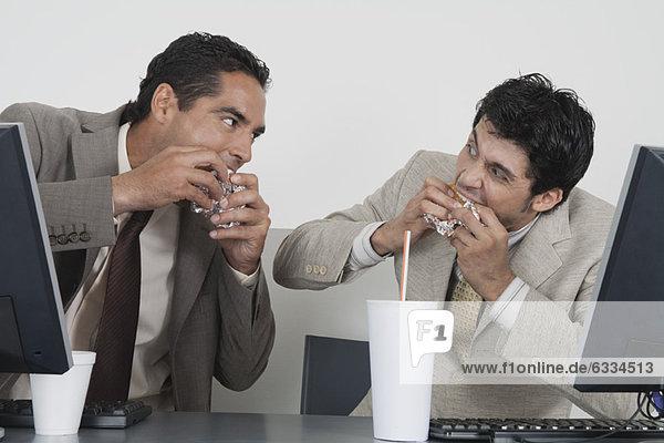 Geschäftsleute essen Fast Food am Schreibtisch im Büro