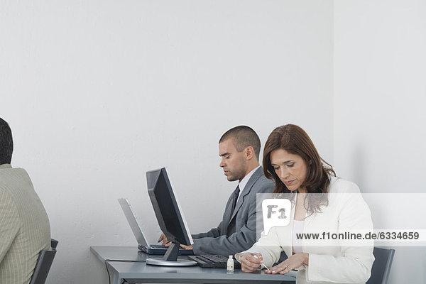 Frau beim Auftragen von Nagellack im Büro  während Kollegen arbeiten