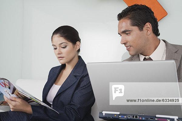 Geschäftsmann mit Laptop-Computer  der rüber schaut  während Geschäftsfrau Zeitschrift liest