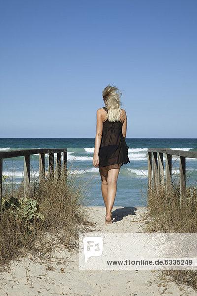 Frau auf dem Weg zum Meer  Rückansicht