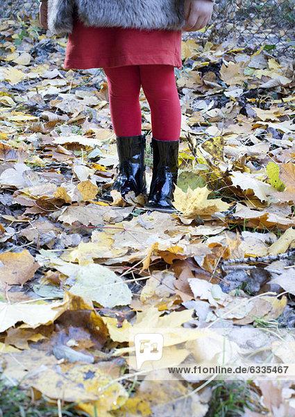 Mädchen auf Herbstblättern stehend  niedriger Schnitt