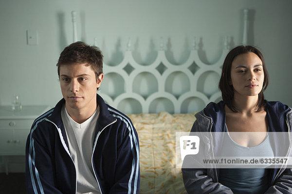 Paar auf dem Bett sitzend  beide in Gedanken wegschauend