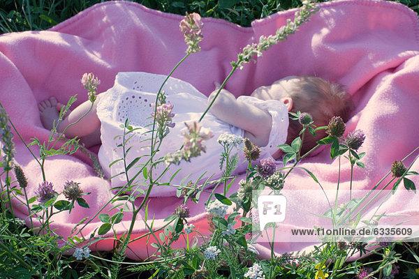 Baby im Freien auf der Decke liegend