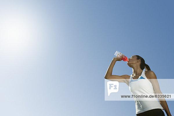 Sportlerin trinkt Sportgetränk  Blickwinkel niedrig