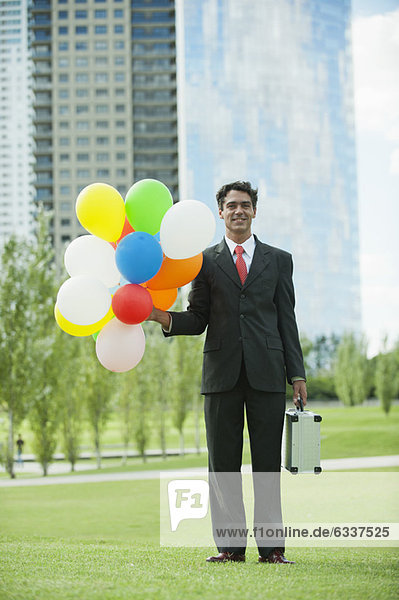 Geschäftsmann  lächeln  Luftballon  Ballon  Bündel  halten Geschäftsmann ,lächeln ,Luftballon, Ballon ,Bündel ,halten
