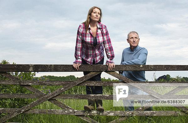 Vater und Tochter auf Holzzaun