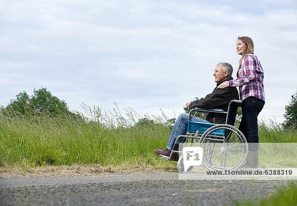 Frau schiebt Vater im Rollstuhl