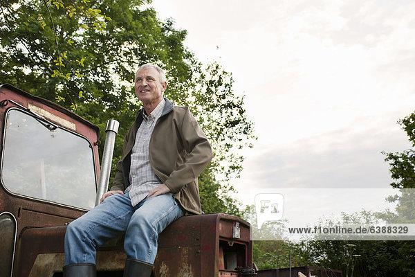 Mann sitzt auf Oldtimer-Traktor im Freien