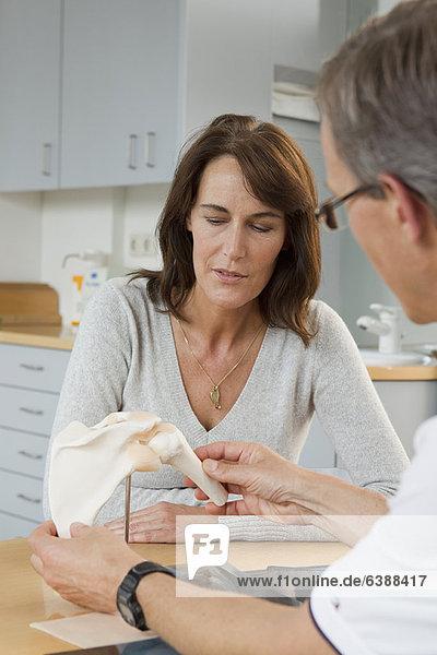 Arzt zeigt Patientenmodell von Knochen