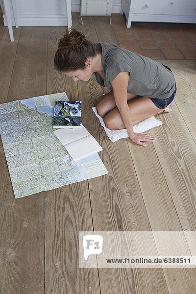 Woman reading maps on floor