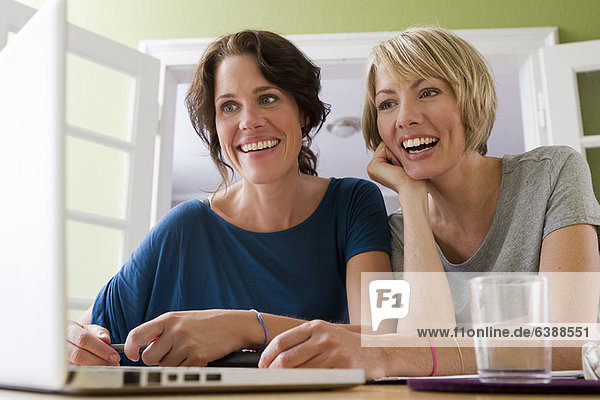 Women using laptop together