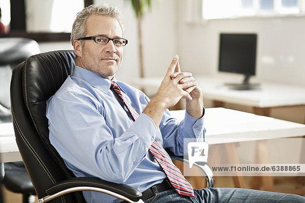 Lächelnder Geschäftsmann am Schreibtisch sitzend