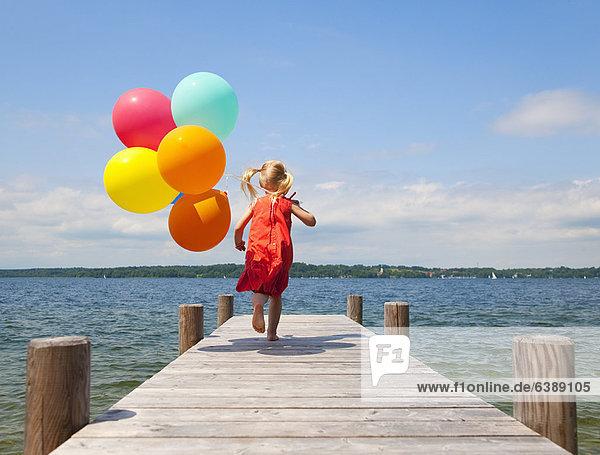 Mädchen hält Luftballons auf Holzpfeiler
