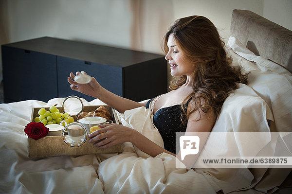 Frau beim Frühstücken im Bett