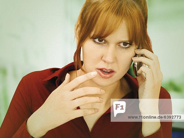 Gestikulierende  verärgerte Geschäftsfrau mit Handy