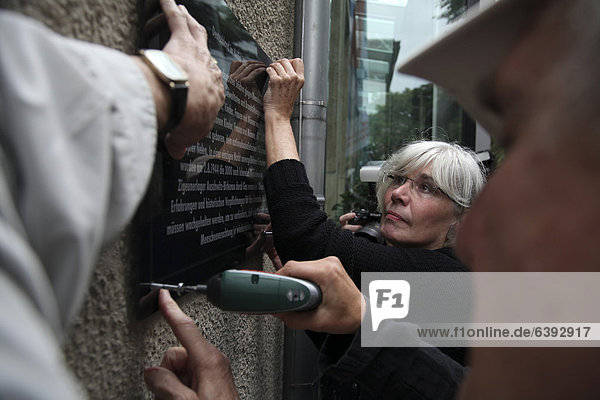 Connie Kerth  national chairman of the Association of Victims of Nazi Persecution  putting a memorial plaque on the facade of the Rostock town hall  20 years after the massive right-wing riots in Rostock-Lichtenhagen in 1992  Rostock  Mecklenburg-Western Pomerania  Germany  Europe