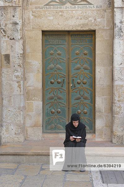Russisch-orthodoxe Nonne hält Andacht vor einer Tür vor der Grabeskirche  Christliches Viertel in der Altstadt von Jerusalem  Israel  Vorderasien  Naher Osten