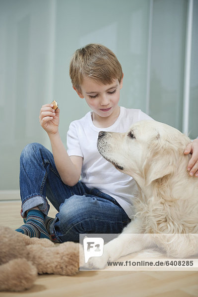 Relaxed boy sitting with his dog on floor