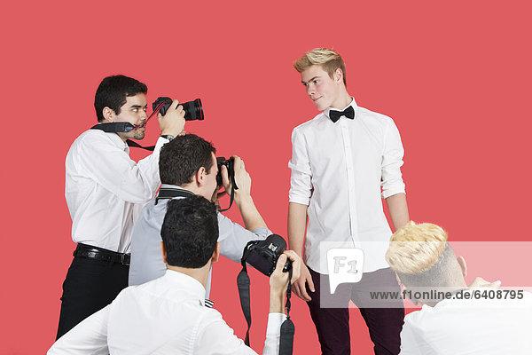 Fotografie  nehmen  über  Hintergrund  rot  Paparazzo  Schauspieler