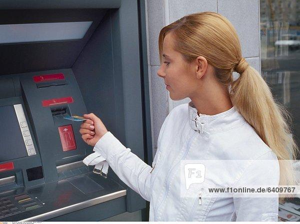 Junge blonde Frau am Bankautomaten