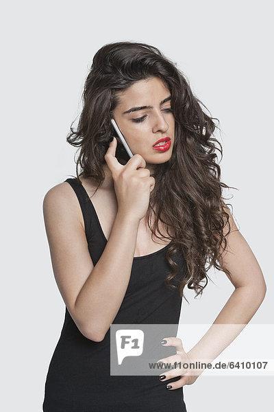 Handy junge Frau junge Frauen benutzen grau ernst über Hintergrund