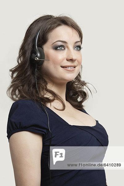 junge Frau junge Frauen grau Kopfhörer Hintergrund Kleidung