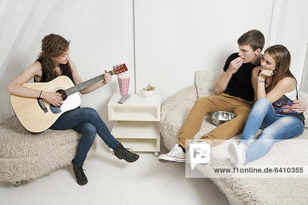 sitzend  Frau  Freundschaft  Couch  Gitarre  jung  spielen