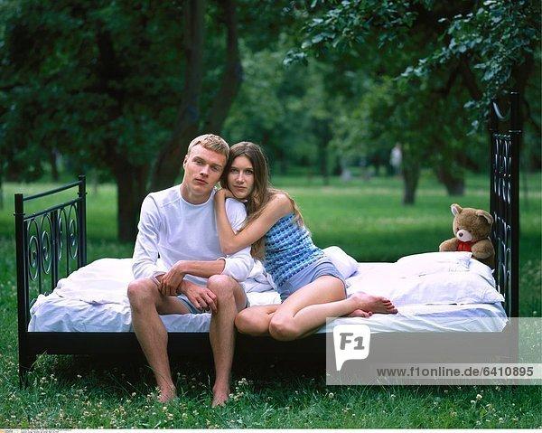 Junges Pärchen auf einem Bett im Park